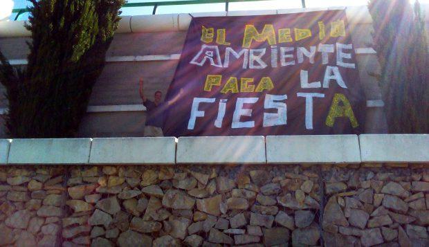 Compañeros de EQUO colocan una pancarta contra la 'huella' del festival 'Alrumbo'.
